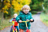 Two active brother boys running on bikes in autumn forest — Stock Photo