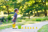 Adorable little girl of 2 playing with yellow rubber ducks in su — Foto Stock
