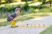 Adorable little girl of 2 playing with yellow rubber ducks in su — Стоковое фото