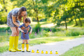 Mother and little adorable daughter in yellow rubber boots — Stock Photo