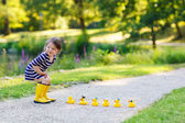 Adorable little child of 2 playing with yellow rubber ducks in s — Стоковое фото