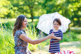 Mother and little adorable daughter with umbrella — Stock Photo