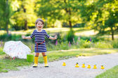 Beautiful little girl of 2 playing with yellow rubber ducks in s — Стоковое фото