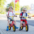 Постер, плакат: Two little siblings children having fun on bikes in city outdoo