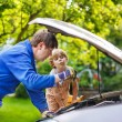 Young father teaching his little son to change motor oil in fami — Stock Photo #51204105