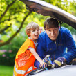 Young father teaching his little son to change motor oil in fami — Stock Photo #51204119