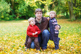 Happy dad with his little sons having fun on sunny autumn day in — Stock Photo