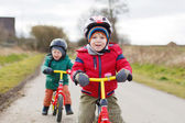 Two little twin toddler boys having fun on bicycles, outdoors — Stock Photo