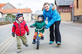Young mother teaching her 2 years old little son to ride a bike — Stock Photo