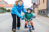 Young mother teaching her 2 years old little son to ride a bike, — Stock Photo