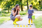 Mother and little adorable child in yellow rubber boots — Stock Photo
