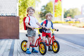 Two little siblings children having fun on bikes in city, outdoo — Stock Photo
