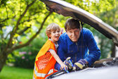 Young father teaching his little son to change motor oil in fami — Stock Photo