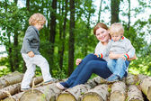 Young mother and two little children having fun in summer forest — Stock Photo