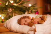 Little cute blond boy sleeping under Christmas tree — Stock Photo