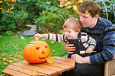 Young man and toddler boy making halloween pumpkin  — Stock Photo