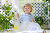 Happy little boy making experiment with colorful water and soap  — Stock Photo