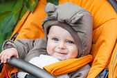 Adorable baby boy in warm winter clothes in stroller — Stock Photo