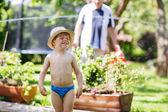 Little toddler boy having fun with splashing water in summer gar — Stock Photo