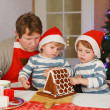 Father and two little sons decorating a gingerbread cookie house — Stock Photo #51490305