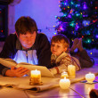 Young father and his little boy reading book by a fireplace on C — Stock Photo #51490427