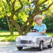 Little boy driving big toy old car, outdoors — Stock Photo #51490429