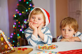 Two little siblings boys happy aboutn selfmade gingerbread cooki — Stock Photo