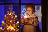 Little boy standing by window at Christmas time — Stock Photo