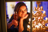 Portrait of young woman through window celebrating New Year's Ev — Stock Photo