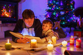 Young father and his little boy reading book by a fireplace on C — Stock Photo