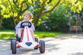 Active little boy driving pedal car in summer garden — Stock Photo