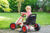 Active little boy driving pedal car in summer garden — Stock Photo