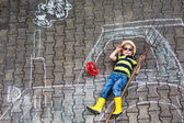 Little boy having fun with tractor picture drawing with chalk — Stock Photo