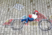 Little boy having fun with race car picture drawing with chalk — Stock Photo
