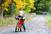 Cute active little boy driving on his bike in autumn forest — Stock Photo
