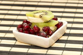 Pieces of fruit banana, kiwi, pomegranate in small platter — Stock Photo