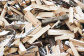 Many wooden logs in pile of snow-covered — Stock Photo