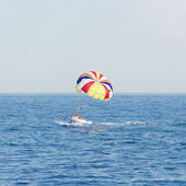 Boat with colorful parachute floating in sea — Stock Photo
