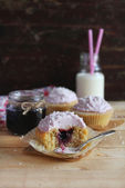 Three cupcakes with blackcurrant jam and coconut — Stock Photo
