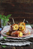 Portion of egg omelette rolls appetizer with spinach leaves wrapped in bacon slices — Stock Photo