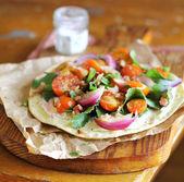 Plochý chléb pšenice s kartou listy, cherry rajčaty, červenou cibulkou a slaninou — Stock fotografie