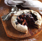Piece of fig and raspberry galette pie with icing sugar — Stock Photo