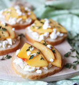 Wheat bread baguette bruschetta with salted greek feta cheese, fresh ripe nectarine slices, thyme and honey drizzling — Stock Photo