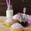 Cupcakes with berry jam filling, cream cheese and coconut on a wooden table — Stock Photo