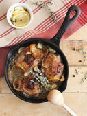Chicken thighs with lemon slices, oregano, garlic and white wine in a pan — Stock Photo
