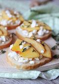 Baguette bruschetta with salted greek feta cheese, fresh ripe nectarine — Stock Photo