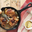 Roasted chicken thighs with lemon slices, white wine sauce, garlic cloves, rosemary and oregano — Stock Photo #34354629
