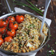 Cod fillet crumble with sesame seeds, sunflower seeds, flax seeds, pine nuts and fresh chopped chives with roasted cherry tomatoes — Stock Photo
