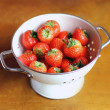 Fresh garden strawberry in a white colander on a wooden surface for summer dessert — Stock Photo