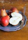 Fresh ripe pears in a plate with knife — Stock Photo